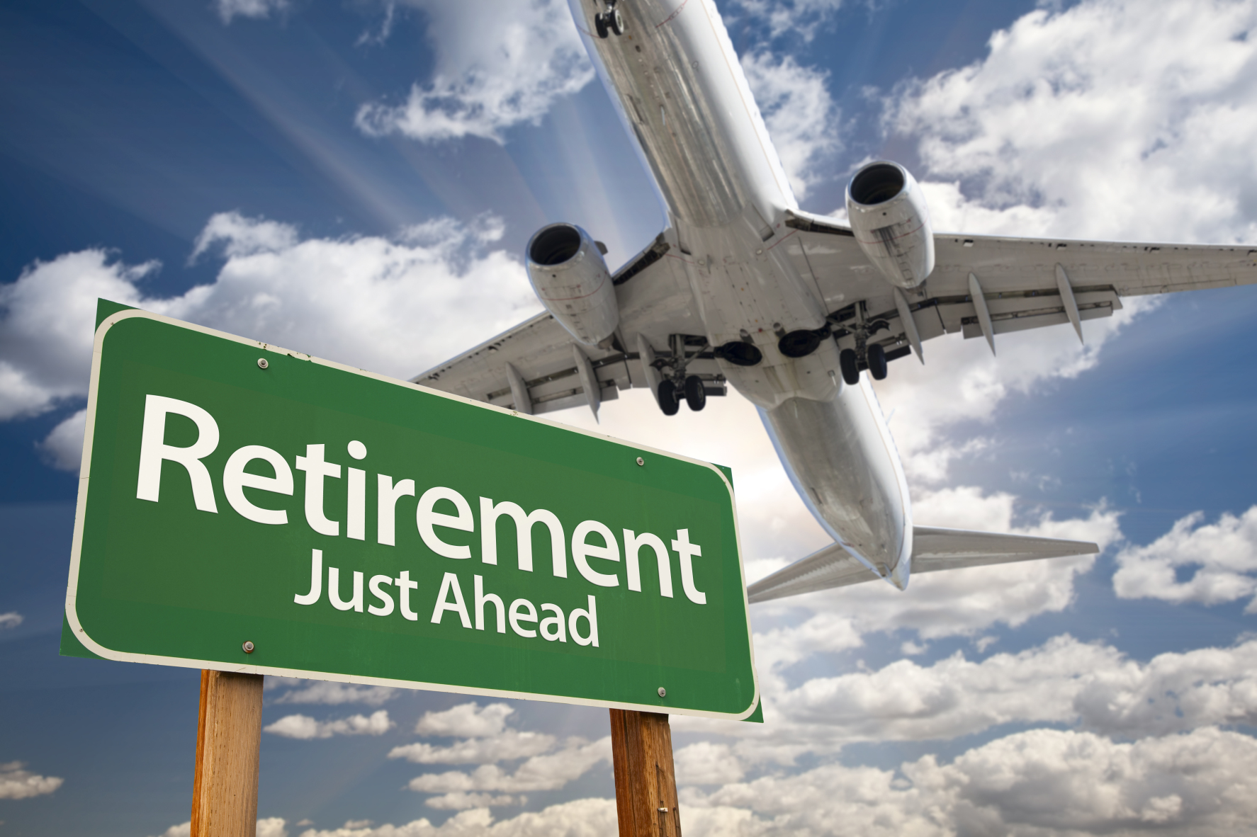Retirement Green Road Sign and Airplane Above